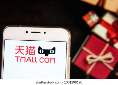 Chinese online shopping website owned by Alibaba Group, Tmall, company logo is seen on an Android mobile device with a Christmas wrapped gifts in the background.