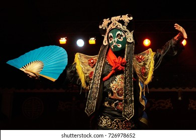 Chinese opera actor performs traditional drama onstage with theatrical costume and mask