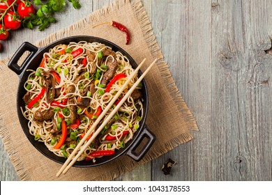 Chinese pasta with beef. Prepared in wok. Wooden background. Top view.