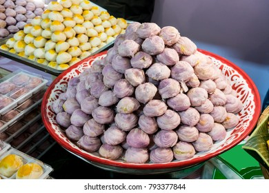 Chinese pastry filled with mung bean and purple yam paste and salted egg. A pile of homemade Thai sweet, called Pia, in traditional tray.