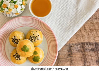 Chinese pastry or moon cake filled with mung bean paste and salted egg yolk on ceramic plate served with tea on wood table in top view flat lay with copy space. Homemade bakery concept.