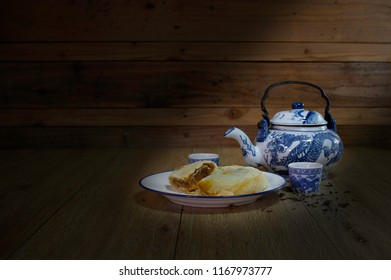 Chinese pastry in white dish with Chinese tea and teapot in dim light room / Select focus and Still life image