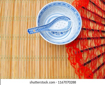 Chinese patterned porcelain soup plate with spoon, on a bamboo placemat. Red lacy fan in the background. Empty space for the text.