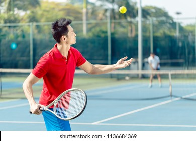 Chinese professional tennis player ready to hit the ball with the racket after tossing while serving in the beginning of a difficult match