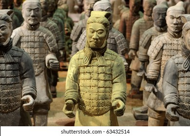 Chinese Qin warrior statues with one gold tinted in a crowd of grey.