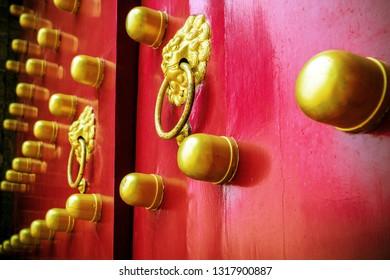 Chinese red gate doors with old metal door handle knocker, Beijing, China.