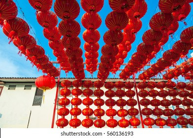 Chinese red lanterns hanging above a house againt blue sky for decoration during the Chinese New Year festival at Chinatown, Ratchaburi, Thailand