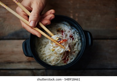 Chinese restaurant menu. Macro shot of hand holding sticks with asian meal on wooden background.