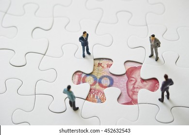 Chinese RMB bill in jigsaw puzzle with men