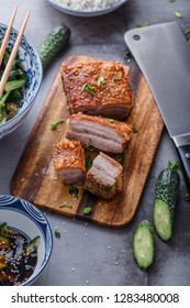 Chinese roasted pork belly on wooden cutting board.