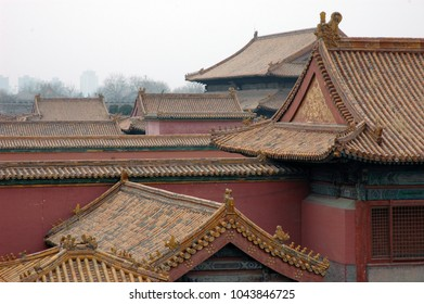Chinese roofs in Forbidden City, Beijing on a cloudy day with modern buildings in background