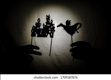 Chinese shadow theater for children projected on a bed sheet, themed of Saint George. The shadows are of cardboard, you can see the hand that manipulates them. dragon, tales, storyteller, castle