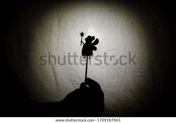 Chinese shadow theater for children projected on a bed sheet, themed of Saint George, April 23. The shadows are of cardboard, you can also see the hand that manipulates them. fairy, tales, storyteller
