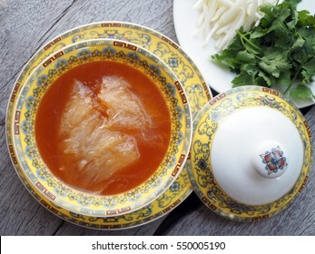Chinese Shark's Fin Soup with brown sauce serve in Royal yellow bowl, decoration with  bean sprouts and Coriander, on grey wooden background.