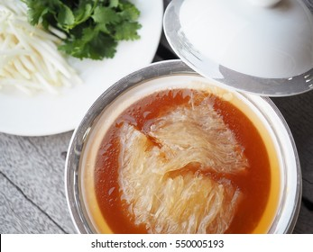 Chinese Shark's Fin Soup with brown sauce serve in Royal white - silver bowl, decoration with  bean sprouts and Coriander, on grey wooden background.