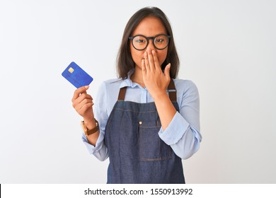 Chinese shopkeeper woman wearing glasses holding credit card over isolated white background cover mouth with hand shocked with shame for mistake, expression of fear, scared in silence, secret concept