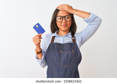 Chinese shopkeeper woman wearing glasses holding credit card over isolated white background stressed with hand on head, shocked with shame and surprise face, angry and frustrated. Fear and upset