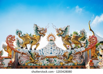 Chinese shrine roof with two Qilin on top. There is a sky and a thin cloud as the background.