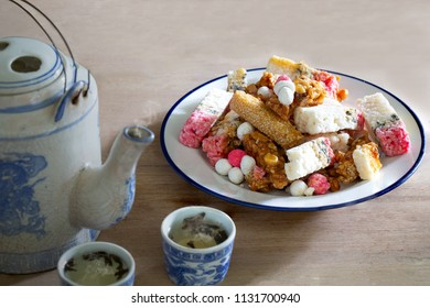 Chinese snack and Chinese tea on old brown wooden table in dim light / Still Life imge and select focus