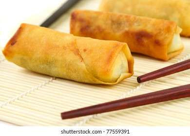 Chinese springrolls with chosticks on the bamboo mat