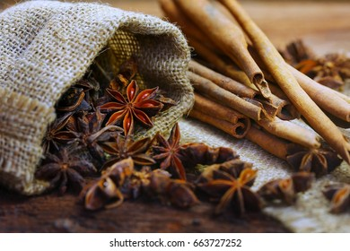 Chinese star anise in sack bag and cinnamon on wooden table, five-spice powder a kind of chinese food, selective focus and toned image.