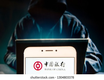 Chinese state-owned commercial baking company Bank of China logo is seen on an Android mobile device with a figure of hacker in the background.