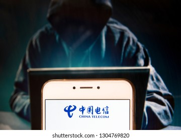Chinese state-owned telecommunications company China Telecom logo is seen on an Android mobile device with a figure of hacker in the background.
