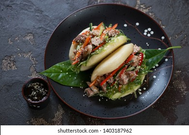 Chinese steamed baozi with chicken and vegetables on a plate, horizontal shot over brown stone background