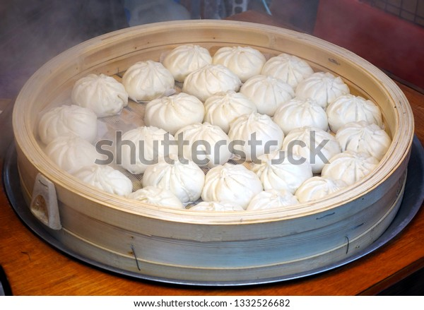 Chinese steamed buns stuffed with meat in a bamboo steamer
