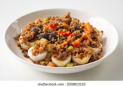 Chinese Steamed Dumplings, Chwee kueh, with topping, steet food and homemade, eaten with chili and soy paste sauce, in white plate on white background, side view and close up