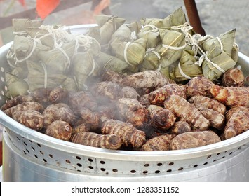 Chinese sticky rice dumplings wrapped in leaves and taro roots in steamer