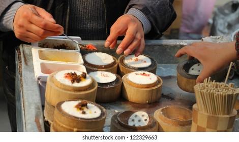 Chinese street food vendor preparing rice snacks