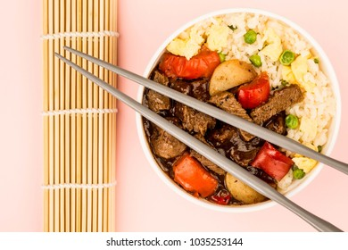 Chinese Style Beef In Black Bean Sauce With Fried Rice Against A Pink Background