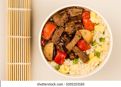Chinese Style Beef In Black Bean Sauce With Fried Rice Against A Grey Background
