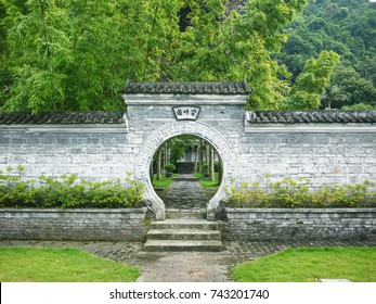 A Chinese style courtyard circular moon gate leads to an inner garden with green bamboos. The Chinese characters on the gate says 'Admiring Bamboo Garden'. County of Xincheng, Guangxi, China