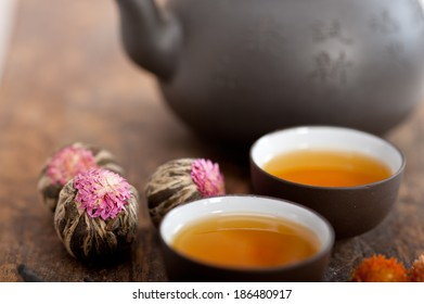 Chinese style herbal floral tea over wood table with raw ingredients