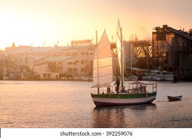 Chinese style sailboat at sunset with Vancouver's Granville Island in the background.
