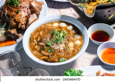 Chinese style soup; or braised fish maw in red gravy with eggs, mushroom, and bamboo shoot in white bowl. Braised Fish Maw in Red Gravy with crab in bowl.