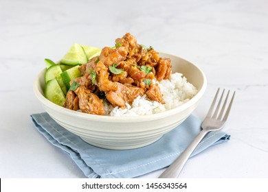 Chinese Style Stir-Fried Chicken with Rice and Cucumber in a White Bowl on White Background.