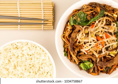 Chinese Style Wok Fried Shanghai Beef Noodles Against A Grey Background