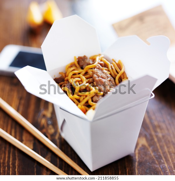 chinese take out with smart phone on table and menu