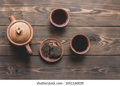 Chinese tea ceremony Asian pressed pu erh black wooden table top view copy space morning energy. Breakfast puer hot drink with caffeine fermented dark crockery tea set clay ceramic pot cups