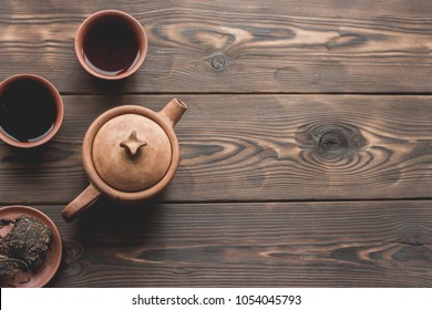 Chinese tea ceremony Asian pressed pu erh black wooden table top view copy space morning energy. Breakfast puer hot drink with caffeine fermented dark crockery tea set room for text