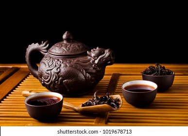 Chinese tea ceremony. Ceramic tea pot and cups with the famous chinese oolong tea Da hong pao on a black background.