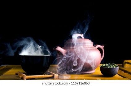 Chinese tea ceremony. Ceramic tea pot and cups with the famous chinese oolong tea Tieguanyin  with vapour on a black background.