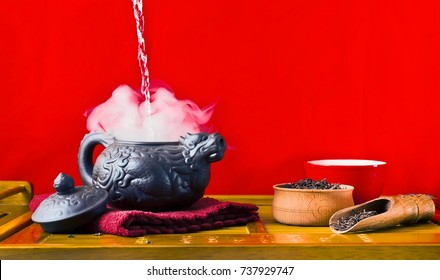 Chinese tea ceremony. Ceramic tea pot, scoop and cups with the famous chinese oolong tea Da hong pao with vapour on a red background.