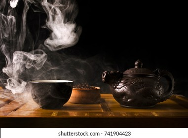 Chinese tea ceremony. Ceramic tea pot and cups with the famous chinese puerh tea with vapour on a black background.