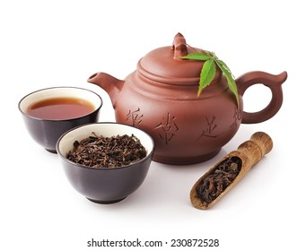 Chinese tea ceremony. Clay teapot with bowls of puer tea and scoop isolated on white background