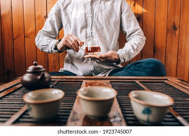 Chinese tea ceremony, a man pours tea into cups on a bamboo table, sunlight