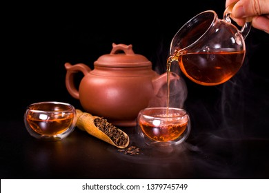 Chinese tea ceremony. Pouring of famous chinese puerh tea from a glass jug into a glass cup with the vapour. Still life on a black background.